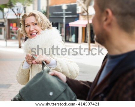 Portrait of woman and robber stealing bag