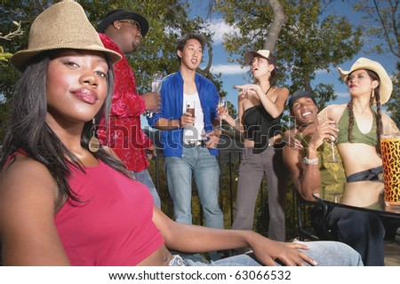 Portrait of woman at party with friends - stock photo