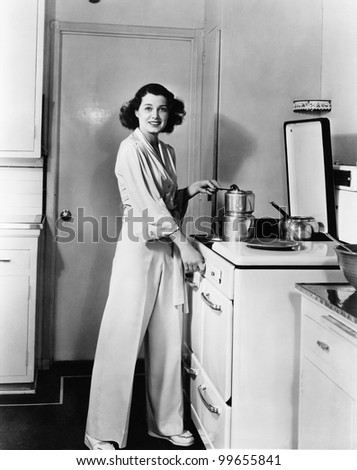 Portrait of woman at stove in kitchen