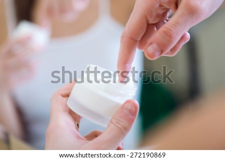 Portrait of woman caring of her skin standing near mirror in the bathroom.