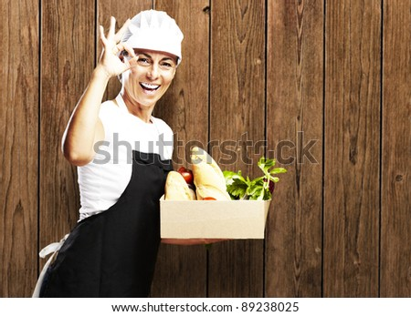 portrait of woman carrying food against a wooden wall - stock photo