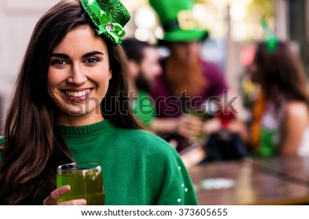 Portrait of woman celebrating St Patricks day with friends and drinks - stock photo
