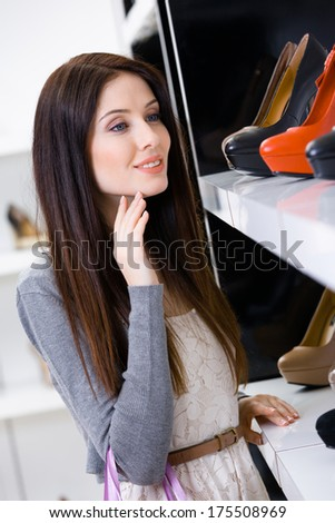 Portrait of woman choosing a pair of footwear in shopping center - stock photo