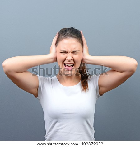 Portrait of woman covering ears with hands against gray background - stock photo