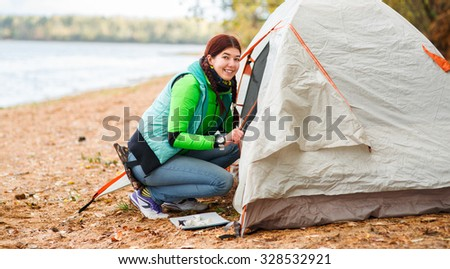 portrait of woman crawls into tent near lake