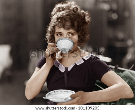 Portrait of woman drinking from teacup - stock photo