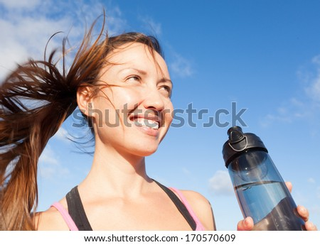 Portrait of woman drinking water outdoor - stock photo