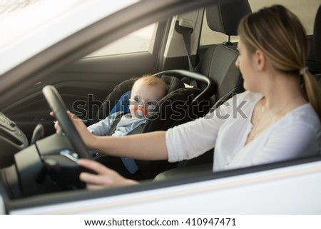 Portrait of woman driving car with baby sitting on front seat