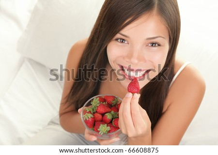 Portrait of woman eating strawberries. Healthy happy smiling woman eating strawberry inside in bed holding a bowl of strawberries. Gorgeous smile on mixed Caucasian Asian female model. - stock photo
