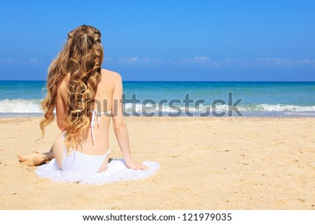 Portrait of woman enjoys in sunny day relaxing and sunbathing on the coast. - stock photo