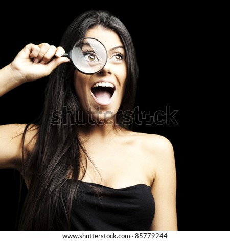 portrait of woman excited looking through a magnifying glass over black background - stock photo