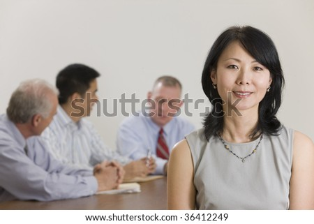 Portrait of woman executive standing in front of her team - stock photo