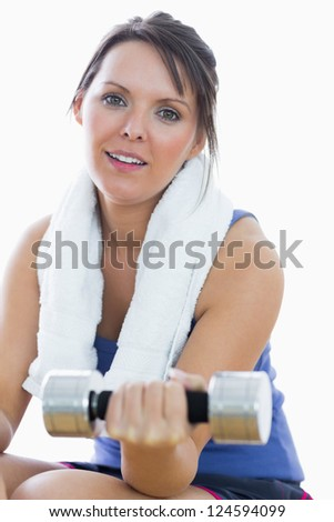 Portrait of woman exercising with dumbbell over white background