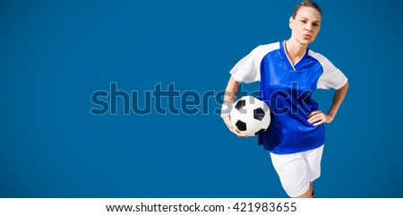 Portrait of woman football player is posing against royal blue