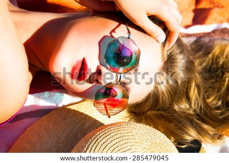 Portrait of woman funky happy and colorful,wearing sunglasses and beach hat,having summer fun during travel holidays vacation.Young multiracial trendy cool hipster woman in bikini lying in the sand. - stock photo