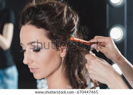 portrait of woman getting hair brushed by hairstylist in beauty salon
