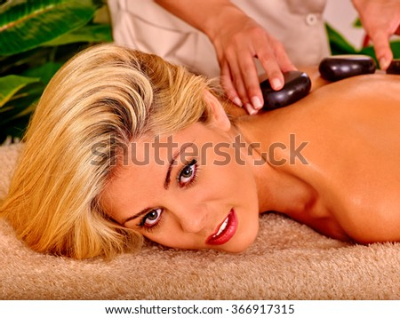 Portrait of woman getting relaxing stone therapy massage. - stock photo