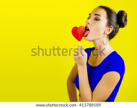 Portrait of woman, girl lick red candy in the form of heart with beautiful make-up on yellow background. Valentine's day, love. Colorful edgy fashion portrait of woman with heart shaped lollipop. - stock photo