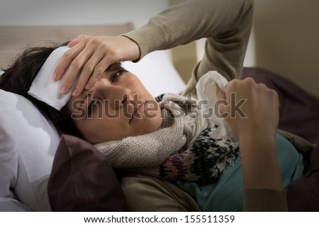 Portrait of woman having fever holding her forehead - stock photo