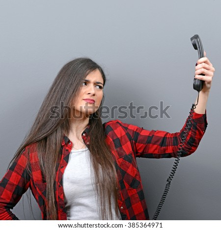 Portrait of woman having unpleasant phone calll against gray background - stock photo