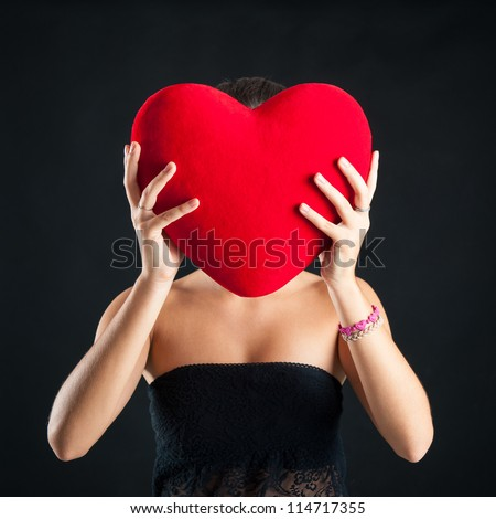Portrait of woman hiding behind red heart against black background. - stock photo