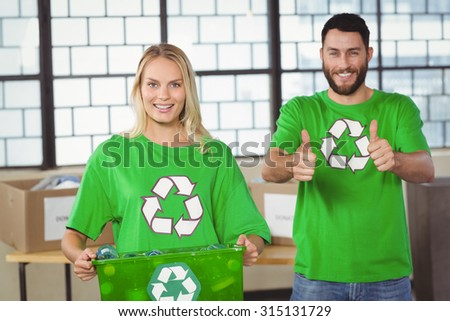 Portrait of woman holding container with colleague showing thumbs up - stock photo