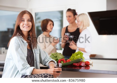 Portrait of woman holding drink with female friends in background - stock photo