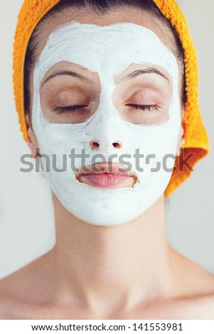 Portrait of woman holding her eyes closed while having a sake and rice face smoothing mask - stock photo