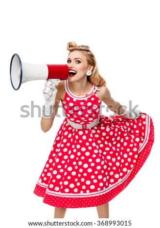 Portrait of woman holding megaphone, dressed in pin-up style red dress in polka dot and white gloves, isolated. Caucasian blond model posing in retro fashion and vintage concept studio shoot. - stock photo