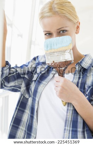 Portrait of woman holding paintbrush in front of face - stock photo