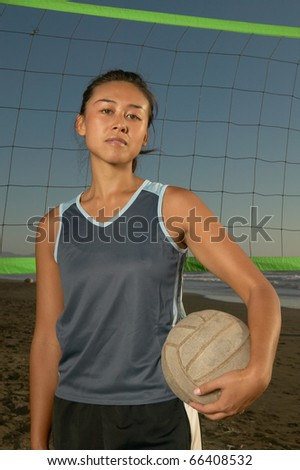 Portrait of woman holding volleyball - stock photo