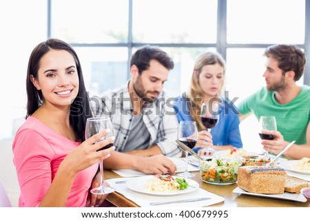 Portrait of woman holding wine glass having meal with friends at home - stock photo