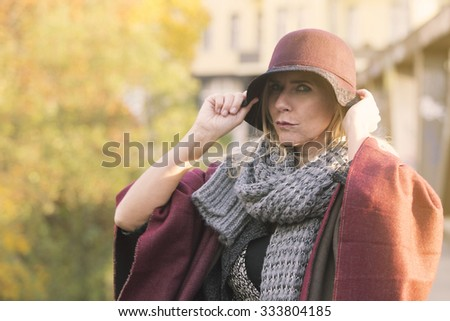 portrait of woman in a hat outdoors next to colorful tree in autumn - stock photo