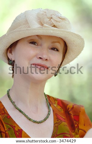portrait of  woman in  age of in  hat on  light green background - stock photo