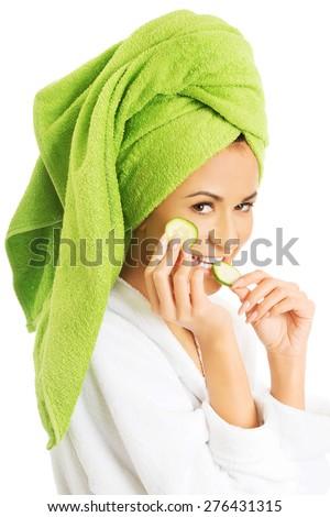 Portrait of woman in bathrobe eating cucumber. - stock photo