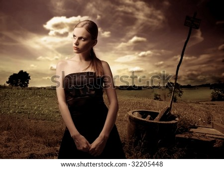 portrait of woman in black elegant dress in the country - stock photo