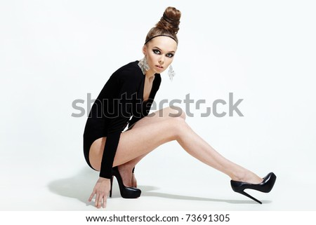 Portrait of woman in black leotard posing on white background - stock photo