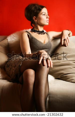 Portrait of woman in cocktail dress in interior on red background - stock photo