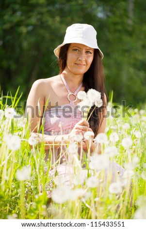 portrait of woman in dandelion plant - stock photo