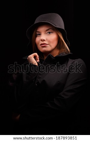 Portrait of woman in elegant coat on black background