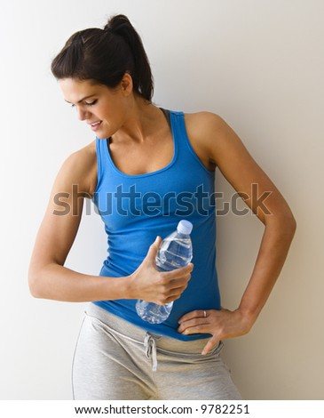 Portrait of woman in fitness attire flexing arm muscle holding water bottle and smiling. - stock photo