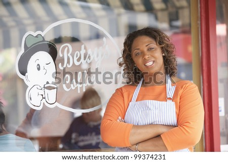 Portrait of woman in front of coffee shop - stock photo