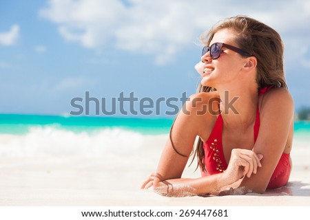 portrait of woman in red swim suit relaxing on tropical beach - stock photo