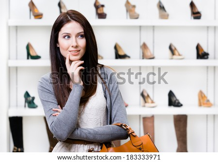 Portrait of woman in shopping center in the section of female stylish shoes. Concept of consumerism and stylish purchase - stock photo