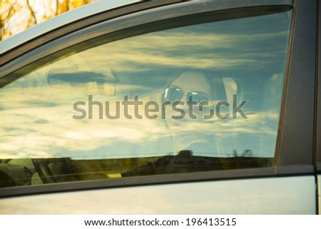 Portrait of Woman in sunglasses and leather gloves looking through the car side window glass with long brown hair on autumn park background  - stock photo