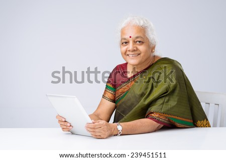 Portrait of woman in traditional Indian clothes sitting at table with a digital tablet - stock photo
