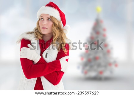 Portrait of woman in warm clothing against blurry christmas tree in room