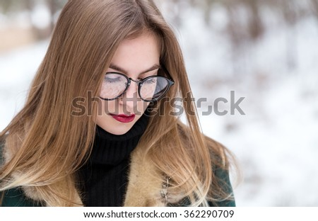 Portrait of woman in winter. Closeup. Woman walks in winter forest. She spends free time outdoors.