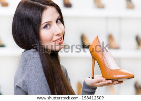 Portrait of woman keeping brown leather high heeled shoe in shopping center - stock photo