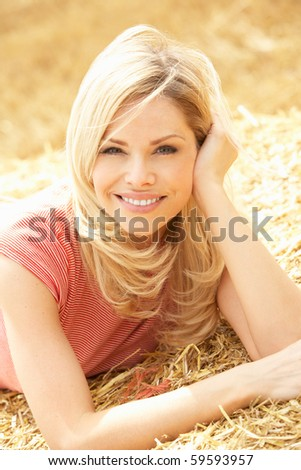Portrait Of Woman Laying In Summer Harvested Field - stock photo